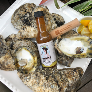 Oysters and oyster shells along with a bottle of Black Eyed Susan Spice Co Death by Chocolate Hot Sauce