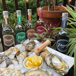 Bottles of Pearl vodka in different flavors surrounding a plate of oysters